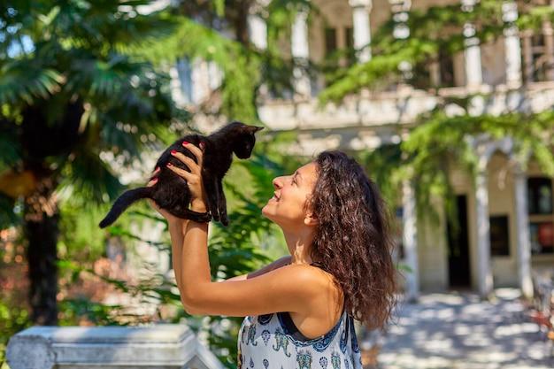 Молодая девушка играет с черным котенком, которого нашла на улице