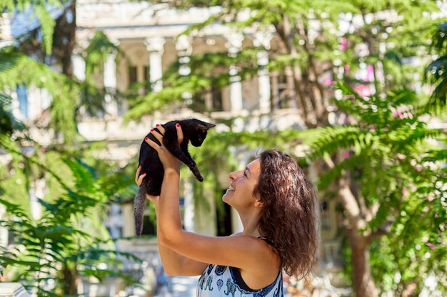 若い女の子が通りで見つけた黒い子猫と遊んでいます。