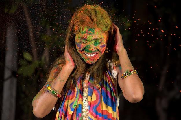 어린 소녀는 색상으로 재생됩니다. 인도 축제 holi의 개념. 컬러 스플래시.
