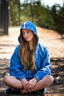 Молодая девушка позирует в джинсовой куртке с капюшоном на фоне сидящего в лесу