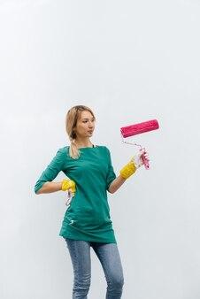 어린 소녀가 흰 벽을 그리기 전에 분홍색 롤러로 포즈를 취합니다.