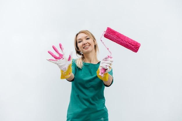 흰 벽을 칠하기 전에 분홍색 롤러를 들고 포즈를 취하는 어린 소녀