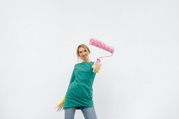 어린 소녀가 흰 벽 앞의 롤러로 포즈를 취합니다. 내부 수리.