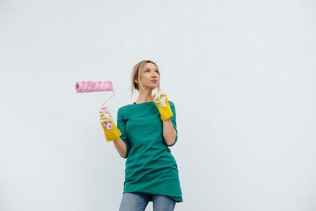어린 소녀가 흰 벽 앞에서 롤러로 포즈를 취합니다.