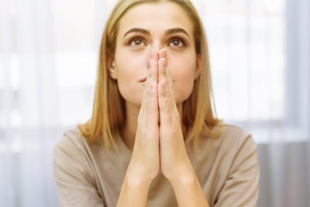 Молодая девушка молится за здоровье людей и за прекращение пандемии, связанной с коронавирусом.