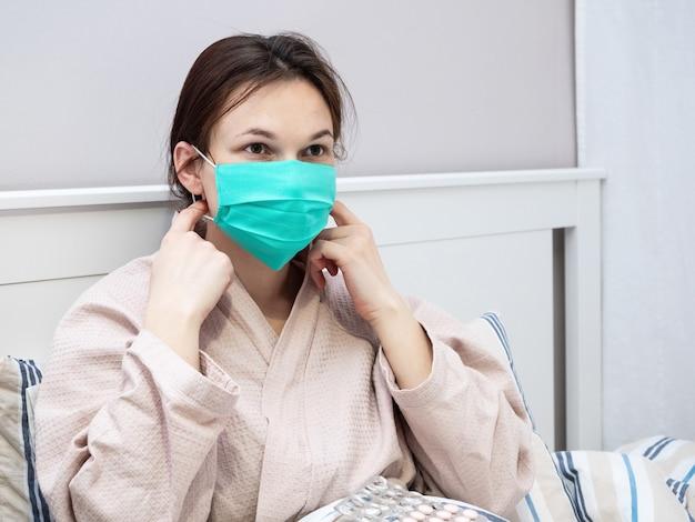 若い女の子は、検疫でベッドに横たわっている間、保護用の医療用マスクを着用します。