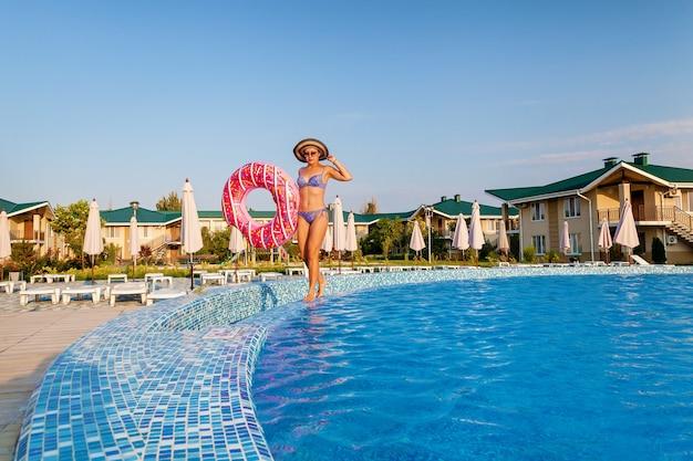 Молодая девушка расслабляется в бассейне. девушка в отпуске.