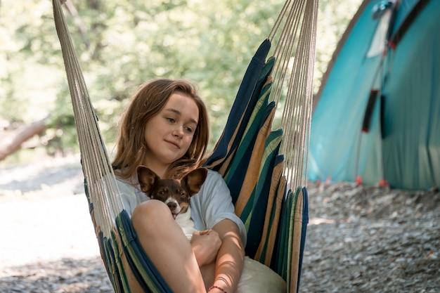 Молодая девушка отдыхает в гамаке со своей собакой. девушка отдыхает в лесу, отдыхает в гамаке. здоровый образ жизни в лесу.