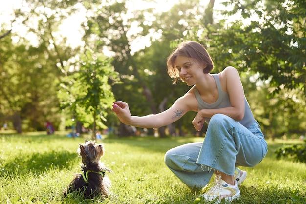 Молодая девушка бегает и играет в зеленом парке со своим йоркширским терьером.