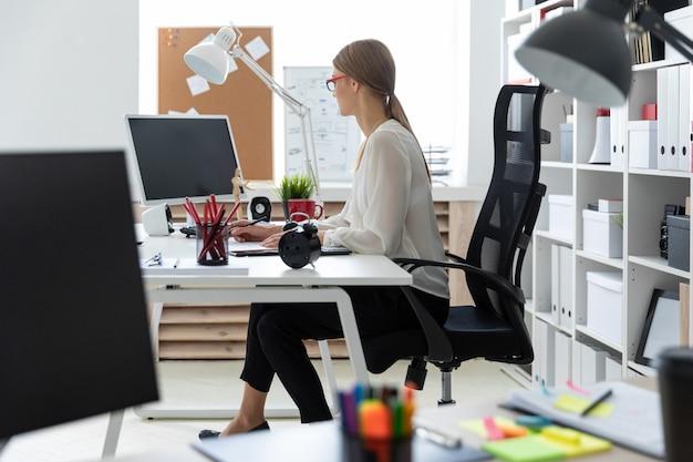 Молодая девушка сидит за компьютерным столом в офисе и держит карандаш в руке.