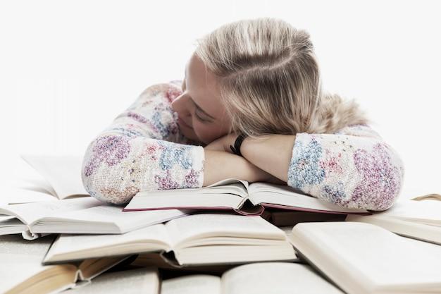 Молодая девушка сидит за столом и спит на книгах. трудности обучения. белый фон.