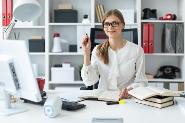 Молодая девушка сидит за столом в офисе и держит карандаш в руке. перед девушкой лежит открытая книга.