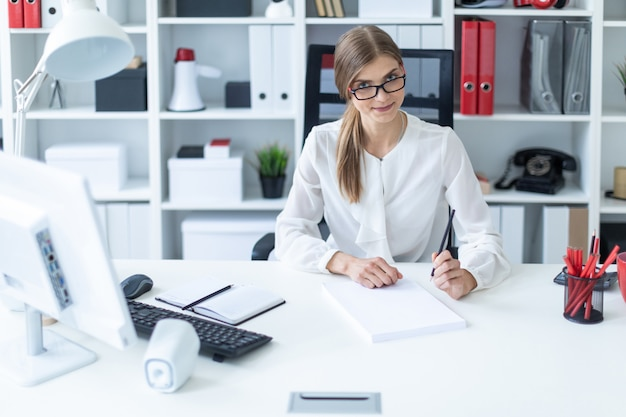 Молодая девушка сидит за столом в офисе и держит карандаш в руке