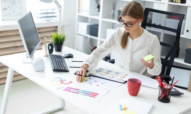 Молодая девушка сидит за столом в кабинете, держит в руке карандаш и клеит наклейку.