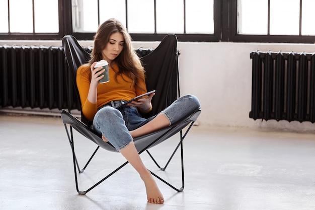 Молодая девушка сидит дома в стильном черном кожаном кресле, держит в руке чашку кофе и планшет. работа и отдых дома