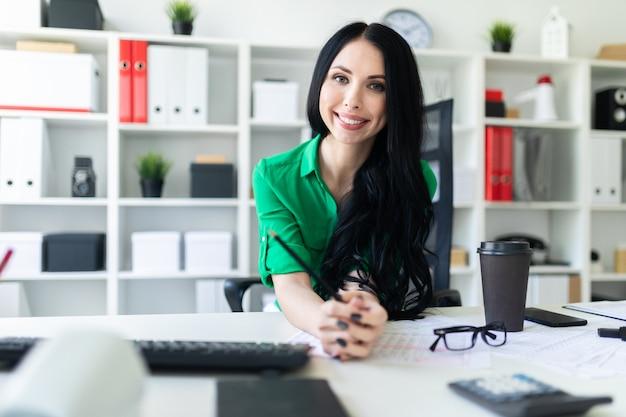 Молодая девушка сидит за офисным столом и держит карандаш в руках.
