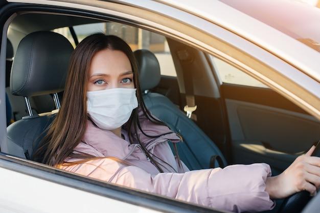 世界的なパンデミックとコロナウイルスの間、少女は車のホイールの後ろのマスクに座っています。検疫。
