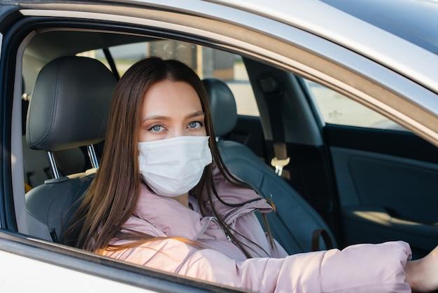 어린 소녀는 글로벌 유행 성 및 코로나 바이러스 동안 마스크에서 자동차의 바퀴 뒤에 앉아 있습니다. 건강 격리.