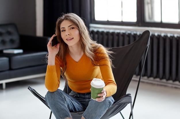 若い女の子はスタイリッシュな黒い革張りの椅子に座って、一杯のコーヒーと電話を彼女の手に持っています。自宅での仕事、コミュニケーション、リラクゼーション