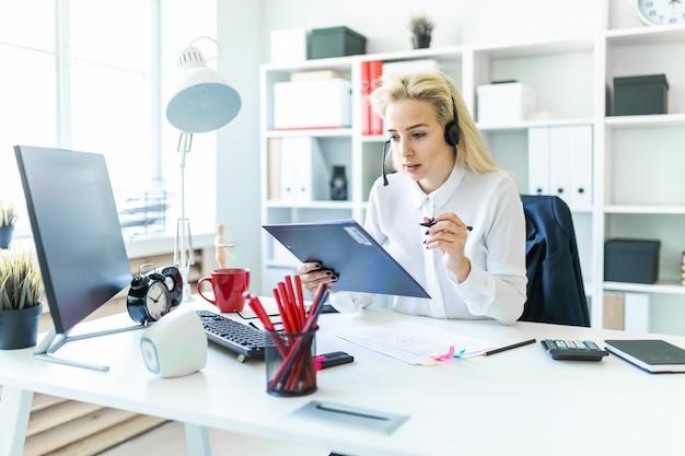 Молодая девушка сидит в наушниках с микрофоном на столе в офисе и делает заметки в документе.