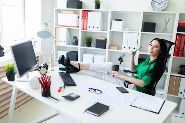 Молодая девушка сидит в кабинете, бросила ноги на стол и держит в руках стакан кофе.