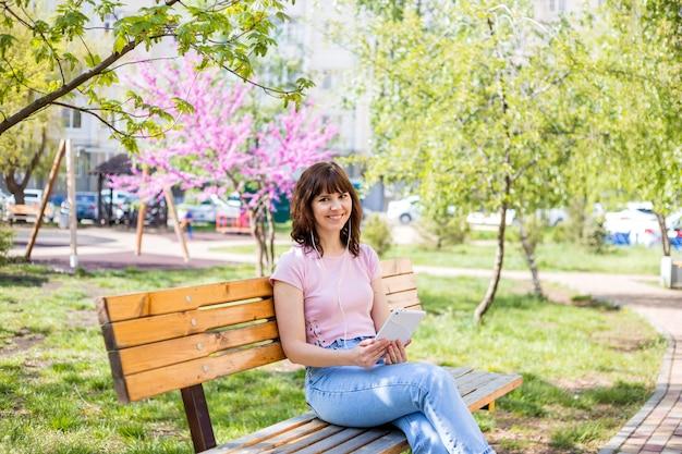 어린 소녀는 공원에서 벤치에 앉아 태블릿을 보인다. 격리에서의 원격 학습.