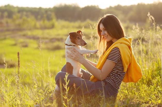 Молодая девушка сидит на траве в лучах заходящего солнца и держит на руках собаку.