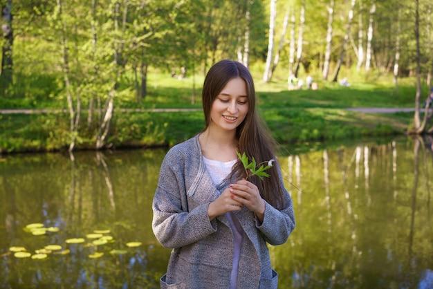 어린 소녀는 그녀의 손에 꽃을 들고 화창한 날에 호수 배경에 달콤하게 서있는 미소