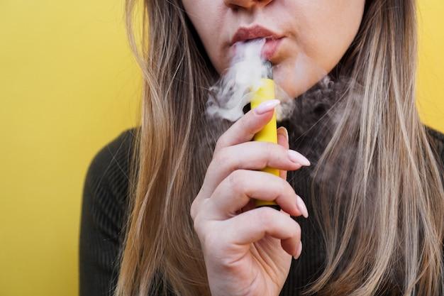 若い女の子が使い捨て電子タバコの明るい黄色の壁を吸う