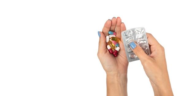若い女の子がパッケージから錠剤を手に絞ります色とりどりの錠剤の山