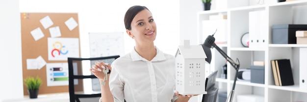 Молодая девушка стоит в кабинете и держит ключи и макет дома.