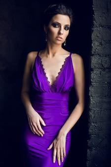 紫色の長いドレスを着て窓の近くに立っている少女