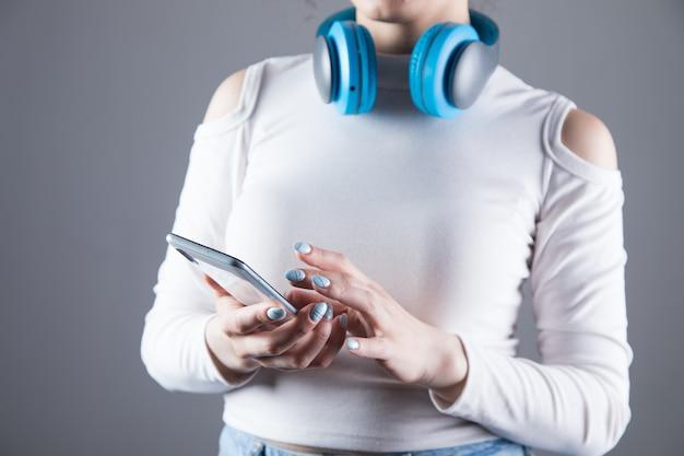 若い女の子が大きなヘッドホンに立って、灰色のシーンで彼女の電話を維持
