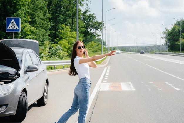 高速道路の真ん中で壊れた車の近くに立っている少女が、車の通過を止めようとしている間、電話で助けを求めます。車の故障と故障。助けを待っています。