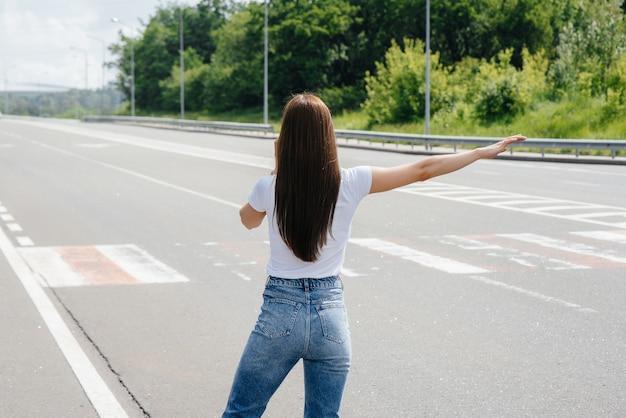 한 소녀가 고속도로 한복판에서 부서진 차 옆에 서서 전화로 도움을 요청하는 한편 지나가는 차들을 막으려 한다. 자동차의 고장 및 고장. 도움을 기다리고 있습니다.