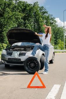 한 소녀가 고속도로 한복판에서 부서진 차 옆에 서서 더운 화창한 날 부러진 바퀴를 바꾸려고 합니다. 자동차의 고장 및 고장. 도움을 기다리고 있습니다.