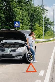 한 어린 소녀가 고속도로 한복판에서 바퀴가 부러진 고장난 차 옆에 서서 더운 날 도움을 기다리며 답답해합니다. 자동차의 고장 및 고장. 도움을 기다리고 있습니다.
