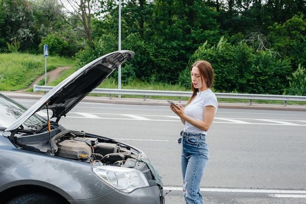 Молодая девушка стоит возле разбитой машины посреди шоссе и зовет на помощь по телефону. отказ и поломка автомобиля. жду помощи.