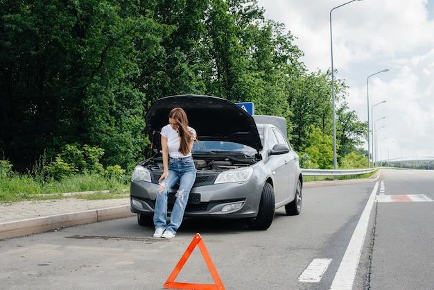한 어린 소녀가 고속도로 한복판에서 고장난 자동차 옆에 서서 전화로 도움을 요청합니다. 자동차의 고장 및 고장. 도움을 기다리고 있습니다.