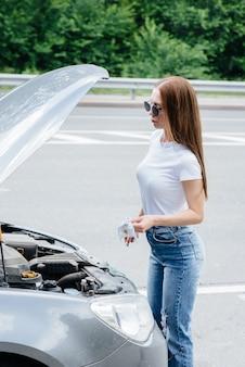 한 어린 소녀가 고속도로 한복판에서 고장난 자동차 옆에 서서 엔진의 오일 레벨을 확인합니다. 자동차의 고장 및 고장. 도움을 기다리고 있습니다.