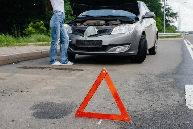 한 어린 소녀가 고속도로 한복판에서 고장난 자동차 옆에 서서 후드 아래를 바라보고 있습니다. 자동차의 고장 및 고장. 도움을 기다리고 있습니다.