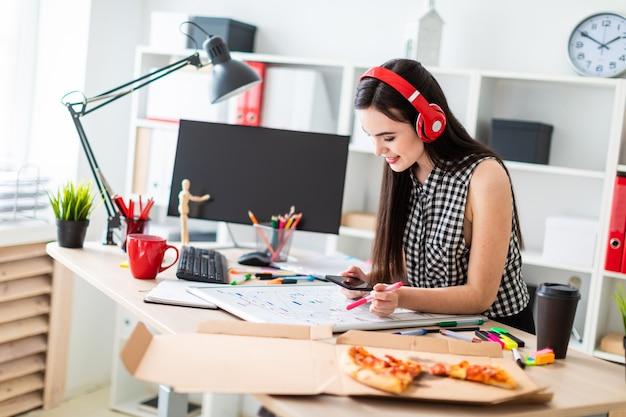 Молодая девушка стоит возле стола и держит в руках маркер и телефон. на столе магнитная доска.