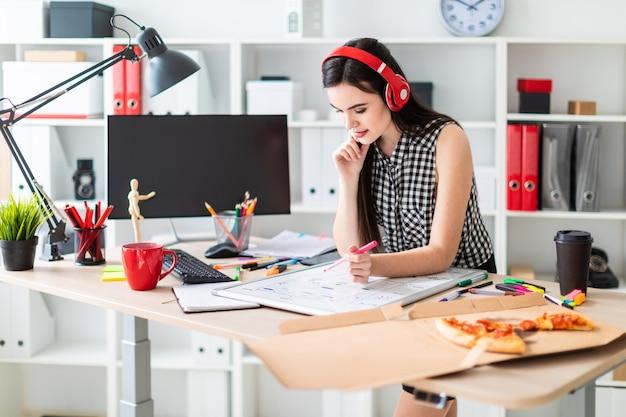 Молодая девушка стоит возле стола и держит маркер в левой руке. на столе магнитная доска.