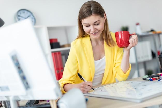 Молодая девушка стоит возле стола и держит в руках красную чашку и маркер. перед девушкой на столе стоит магнитная доска
