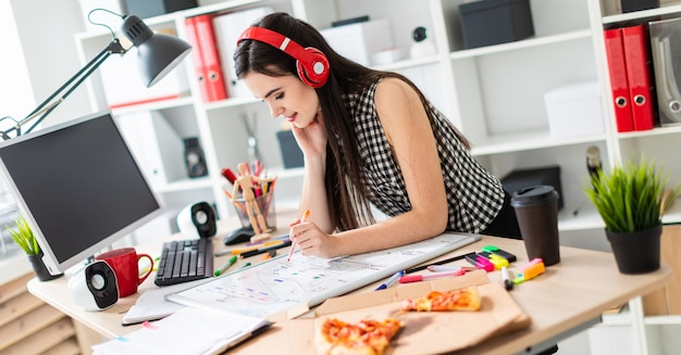 Молодая девушка стоит возле стола, держит в руке оранжевый маркер и смотрит на магнитную доску. на голову девушки надевают наушники.