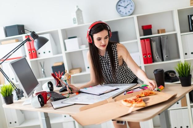 Молодая девушка стоит возле стола, держит в руке зеленый маркер и берет кусок пиццы. перед девушкой на столе стоит магнитная доска. на голову девушки надевают наушники.