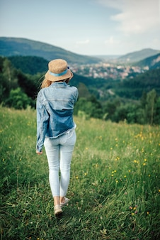 Молодая девушка стоит на лугу на вершине горы и смотрит на горы в соломенной шляпе. вертикальное фото девушки на фоне гор.