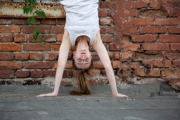 Молодая девушка стоит на руках вверх ногами