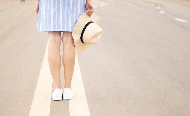 ピンクの帽子と白いスニーカーの分割帯の道路に立つ少女。