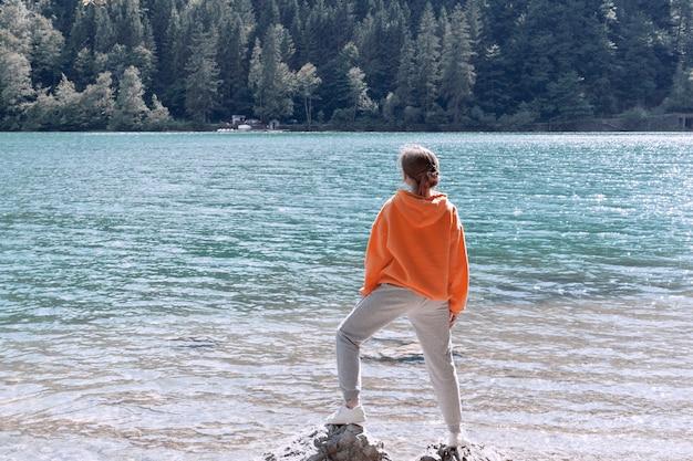 어린 소녀가 운동복을 입고 산 호수 기슭에 서서 거리를 들여다 본다.